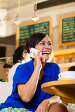 Young woman in an Asian coffeeshop Royalty Free Stock Photos