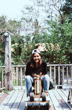 Young woman asian she rides a toy wood horse on the carousel wit Royalty Free Stock Images