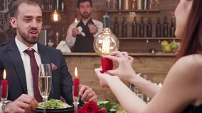 Young woman asking her boyfriend to get married at a romantic dinner stock footage