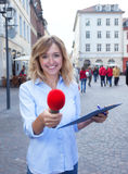 Young woman asking for opinion in the city. With street and buildings in the background royalty free stock photo