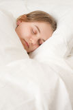 Young woman asleep in bed Royalty Free Stock Image