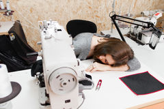 Young woman is asleep by her sewing machine Royalty Free Stock Photo