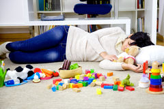 Young woman asleep in the middle of toys of her children Stock Photography