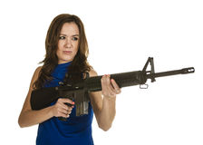 Young woman with assault rifle. An attractive young woman in blue blouse holding an assault rifle threateningly on white background Stock Image