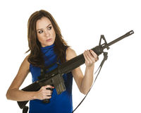 Young woman with assault rifle. An attractive young woman in blue blouse holding an assault rifle on white background Stock Photo