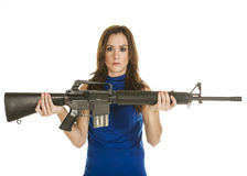 Young woman with assault rifle. An attractive young woman in blue blouse holding an assault rifle on white background Stock Photos