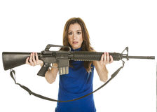 Young woman with assault rifle. An attractive young woman with concerned look in blue blouse holding an assault rifle on white background Royalty Free Stock Photography