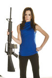 Young woman with assault rifle. An attractive young woman with concerned look in blue blouse holding an assault rifle on white background Stock Images