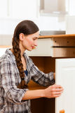 Young woman is assembling a cupboard Stock Photography