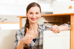 Young woman is assembling a cupboard Royalty Free Stock Photo