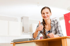 Young woman is assembling a cupboard Royalty Free Stock Photos