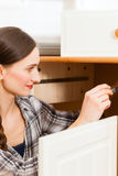 Young woman is assembling a cupboard Stock Photos