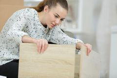 Young woman assembling parts furniture. Young woman assembling the parts of the furniture Stock Image