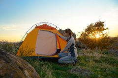 Young Woman Assembling the Tent at Sunset in the Mountains. Adventure and Travel. stock photography