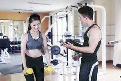 Young woman assisted by her trainer in gym center. Picture of young women assisted by her trainer while doing a workout with dumbbells in the gym center royalty free stock image