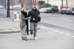 Woman Assisting Blind Man On Street. Young Woman Assisting Blind Man With White Stick On Street Royalty Free Stock Photography