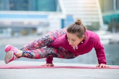 Young woman in Astavakrasana pose against the city and river Stock Photos