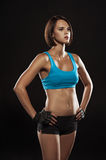 Young woman athlet muscle body portrait in gym. Young woman athlete muscular portrait isolated on black in gym stock image