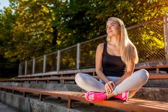 Young woman athlete having rest after running on sportsground in summer. Happy girl sitting on bench and relaxing stock image