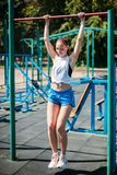 Young woman athlete pulled up on bar on the gym on outdoors stock image