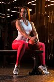 Young woman athlete is resting on the bench after the exercises with ball in gym stock photography