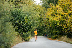 Young woman athlete running in autumn forest. On road from asphalt Stock Image