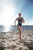 Young woman athlete running out of the sea Royalty Free Stock Photo