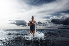 Young woman athlete running out of water Stock Photography