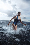 Young woman athlete running out of the water Royalty Free Stock Photography
