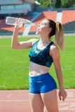Sportswoman drinking water at the stadium royalty free stock image