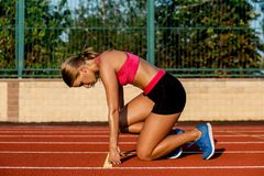 Young woman athlete at starting position ready to start a race on racetrack. Young woman athlete at starting position ready to start a race. Female sprinter royalty free stock photo