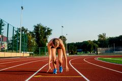 Young woman athlete at starting position ready to start a race on racetrack. Royalty Free Stock Photos