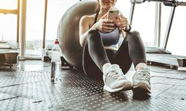 Young woman athlete using cell phone at gym. Young woman in sportswear checking phone while resting after workout on floor. Beautiful fit girl messaging with stock image
