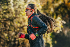 Young woman athlete with watch and headphones running through woods Royalty Free Stock Image