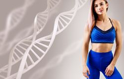 Young woman with athletic body standing among DNA chains. Metabolism concept royalty free stock photo