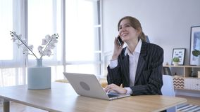 Young Woman Attending Call at Work, Talking on Phone. High quality Royalty Free Stock Image