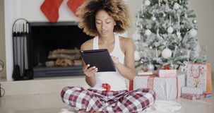 Young woman attending to Xmas social media. Trendy young African woman sitting on the floor in front of the Christmas tree attending to Xmas social media on her stock video footage