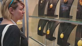 Young woman attends an exhibition of jewelry made of amber stock video footage