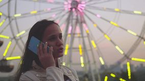 Young woman at an attractions park arcade talk by smartphone against the backdrop of glowing ferris wheel in slowmotion. 1920x1080. hd stock video