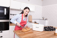 Young woman attractive cutting bread in kitchen. Royalty Free Stock Images