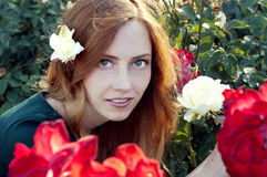 Young woman with auburn hair sitting in the rose garden Royalty Free Stock Photography