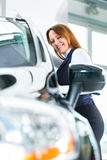 Young woman with auto in car dealership Royalty Free Stock Image