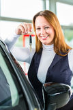 Young woman with auto in car dealership Royalty Free Stock Images
