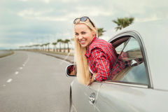 Young woman auto traveler on the highway Stock Photos
