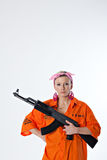 Young woman with automatic rifle. Dangerous young woman in orange shirt holding automatic rifle Royalty Free Stock Images