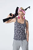 Young woman with automatic rifle. Dangerous young woman with automatic rifle holding one hand in her pocket Royalty Free Stock Photography