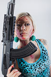 Young woman with automatic rifle. Close up of a dangerous young woman covered in blood, holding automatic rifle Royalty Free Stock Photography