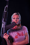 Young woman with automatic rifle. Close up of a dangerous young woman covered in blood, holding automatic rifle Stock Images