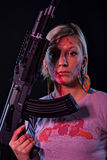 Young woman with automatic rifle. Dangerous young woman holding automatic rifle Stock Photos