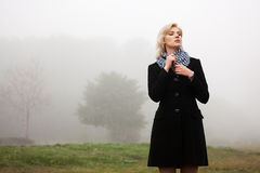 Young woman in autumn foggy field Royalty Free Stock Images